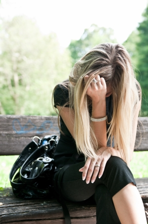 Young beautiful woman siting on bench in park in depression
