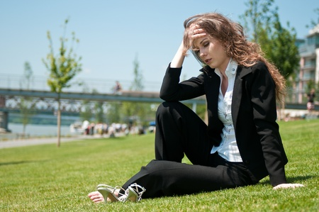 Young worried business woman siting outdoors in grass - head in hand Stock Photo - 8957640