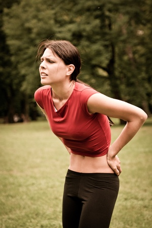 injure: Backpain - sportswoman in pain Stock Photo
