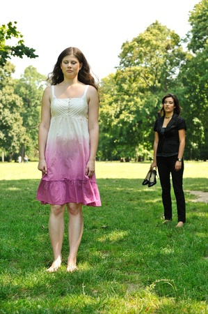 One girl is offended and her friend is calling for her - outdoors in park photo