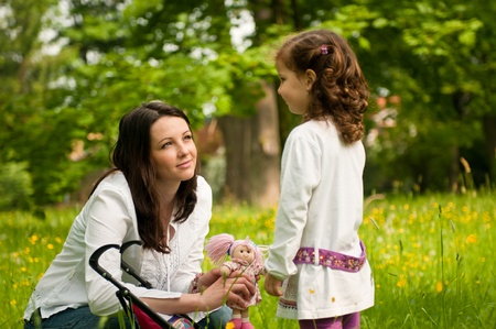Mother spending time with her cute girl outside in park - nostalgy mood Stock Photo