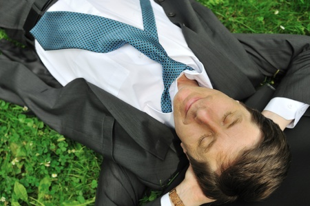 Senior people series - mature business man lying in grass and relaxing photo