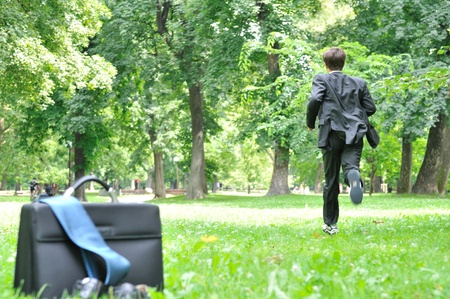 Escape from civilization concept - business man running in park away from bag, shoes and tie photo