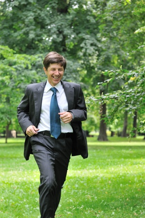 Escape from civilization - smiling senior business man running in park                             photo
