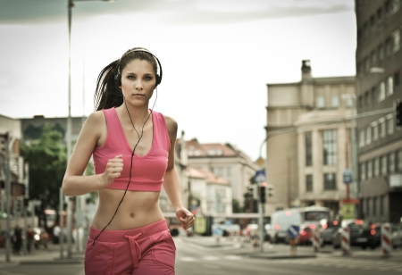 Runner (young beautiful woman) training in street with (traffic background - cars and buildings) photo