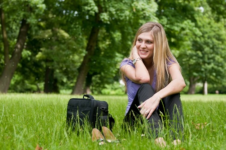 grassfield: Young smiling business woman siting in grass and relaxing after work Stock Photo