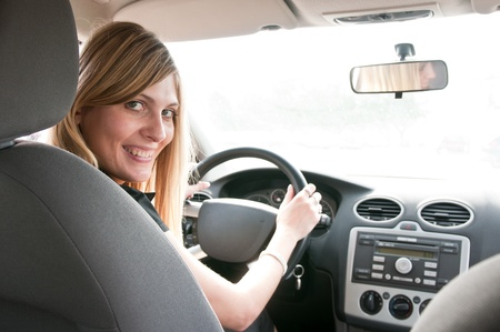 Portrait of young smiling woman siting behind steering wheel inside car photo