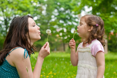 dandelion seed: Mother with small daughter blowing to dandelion - lifestyle outdoors scene in park