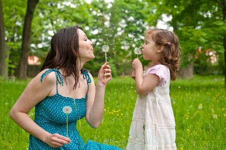 blow: Madre con la figlia piccola che soffia a dandelion - scene di vita all'aperto nel parco Archivio Fotografico