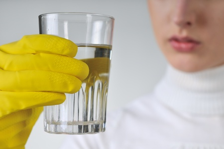 Young woman in yellow hygienic gloves holding glass of water - concentration                             photo