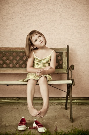 simple girl: Outdoors portrait of small cute child with hanging legs - sepia tone Stock Photo