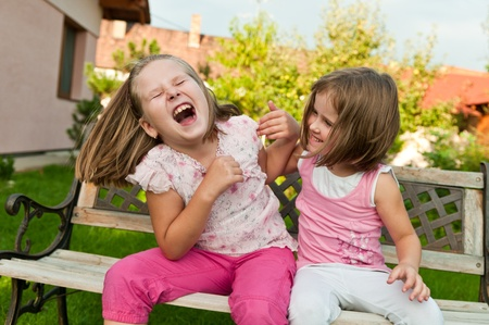 tickling: Two small girls (sisters) larking in backyard sitting on bench Stock Photo