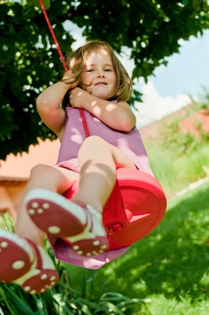Happy small cute girl swinging on seesaw in garden behind family house Stock Photo