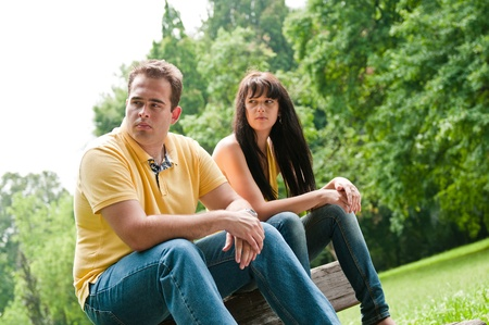 negative emotion: Young couple sitting outdoors on bench having relationship problems