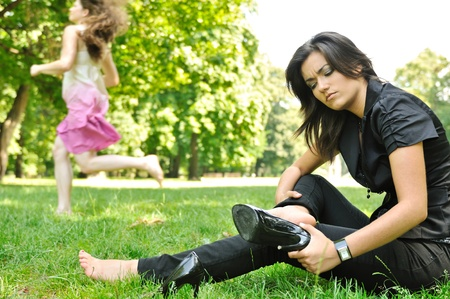 high contrast: One woman running barefoot in park and second is taking her shoes off Stock Photo