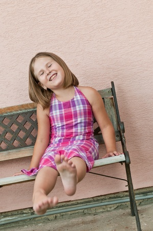 simple girl: Portrait of cute child sitting on bench and stretching barefoot legs