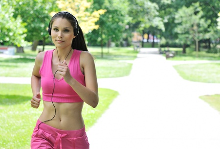 Young person (woman) with headphones listening music running outdoors in park on sunny day photo