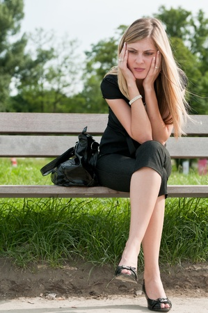 Young beautiful woman siting on bench in park in depression photo