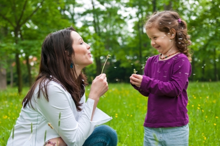 mother with child: Mother with small daughter blowing to dandelion - lifestyle outdoors scene in park