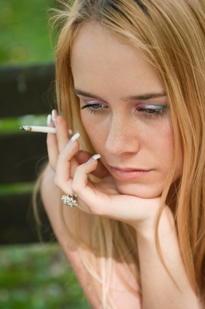 troubled teen: Lifestyle portrait of young worried and depressed woman smoking cigarette outdoors