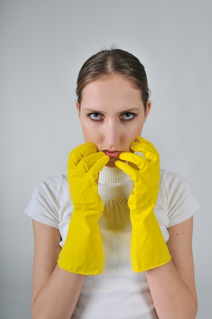 Young woman wearing yellow work gloves with thoughtful expression photo