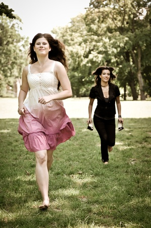 Two friends run barefoot in park on grass - freedom concept photo