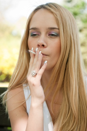 cigarette: Young teen person smoking cigarette outdoors
