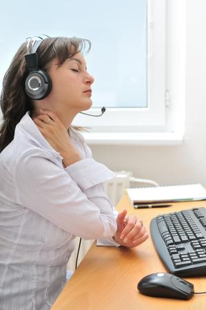 blusa: Empresario joven llevaba auriculares sufriendo dolor de cuello. Vista de perfil.