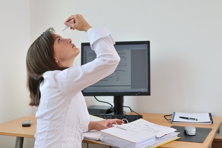 cure prevention: Detail of young business person (woman) applying eye drops on workplace - computer on table Stock Photo