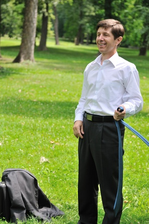 loose: Escape from civilization - smiling senior business man putting off tie and relaxing in fresh green park Stock Photo