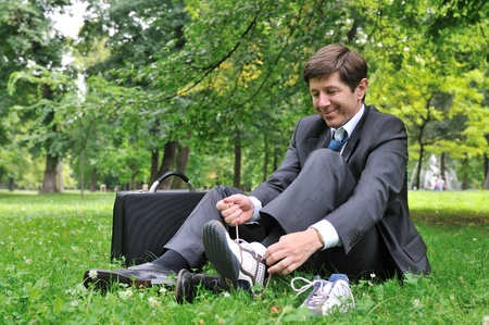 shoes off: Senior business man changing working shoes for sports shoes in park (siting on grass)