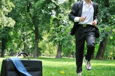 running businessman: Training - business man running in park, bag and tie laid on grass
