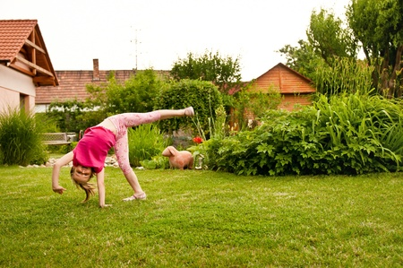 excercise: Child doing cartwheel in backyard Stock Photo