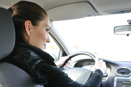 Lifestyle shot of young cheerful woman driving car - rear view Stock Photo