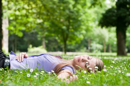 Relaxed young person (teenage girl) lying in grass and flowers with stretched hand - closed eyes photo