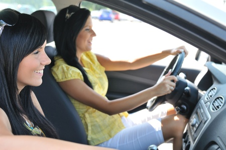 woman driving car: Youth lifestyle - two smiling friends (women) driving in car Stock Photo