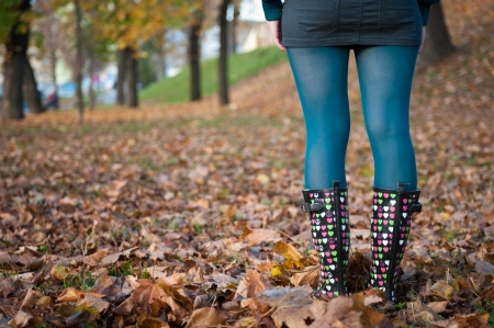 Detail of woman in wellington boots standing in fallen leaves in autumn - rear view photo