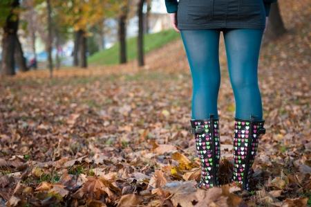 wellington: Detail of woman in wellington boots standing in fallen leaves in autumn - rear view