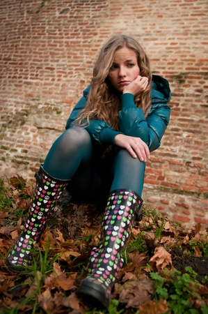 Portrait of young worried woman in rubber boots - autumn lifestyle photo