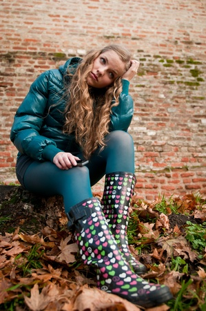 wellington: Portrait of young worried woman in rubber boots - autumn lifestyle Stock Photo