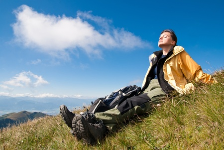 sunning: Young person relaxes and sunning on hiking in mountains