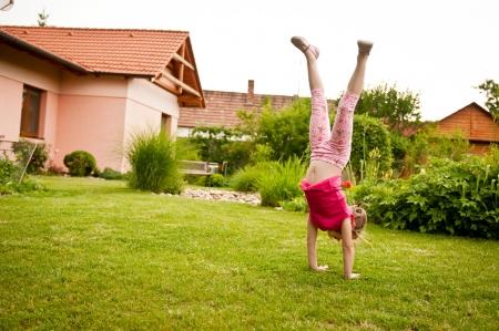 Child doing handstand in backyard Stock Photo - 10461404