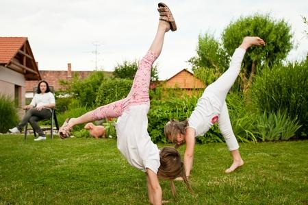 Children doing cartwheels in backyard photo