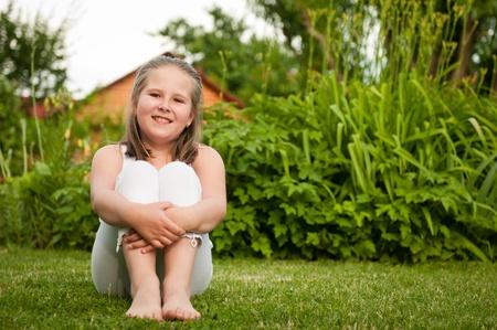 assis par terre: Portrait d'enfant souriant Backyard (fille de neuf ans) assis sur l'herbe Banque d'images