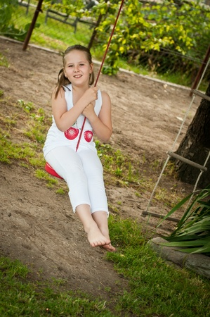 young girl barefoot: Child swinging on seesaw