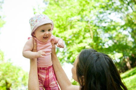 Happy mother lifting her beautiful child outside in park Stock Photo - 10461408