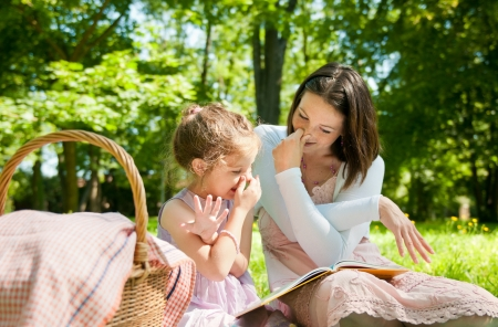 candid: Mother with child are playing while reading book and imitating elephant Stock Photo