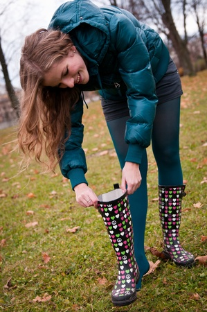 wellington: Smiling young woman looking in rubber boots - outdoors autumn Stock Photo