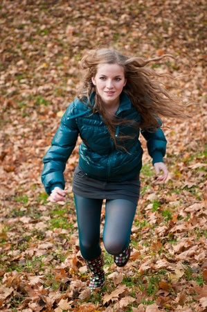 Autumn pleasure - young woman runing photo