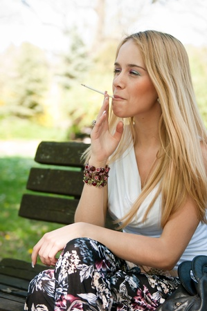 sucking: Young teen person smoking cigarette outdoors